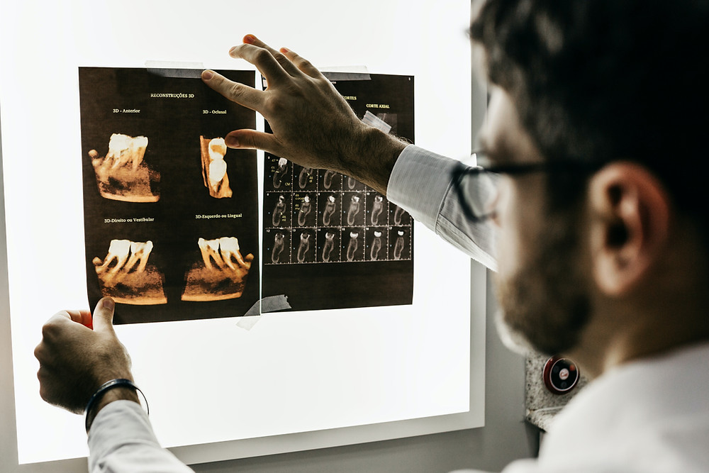 Dentist looks at x-rays