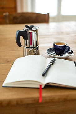 Open blank journal with a cup of coffee and individual coffee pot Image by Elena Kloppenburg