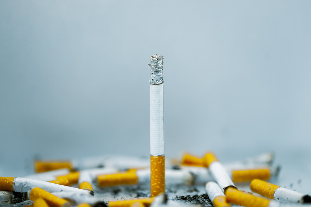 A pile of cigarettes with one of them standing upright.