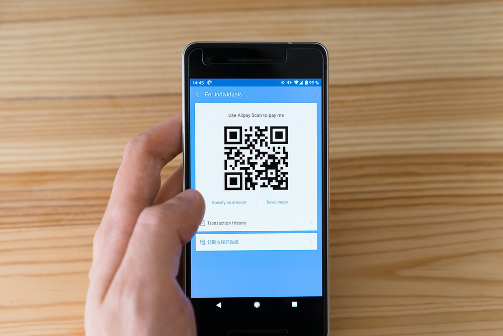 A  person holding a mobile phone with a QR scan code on it.