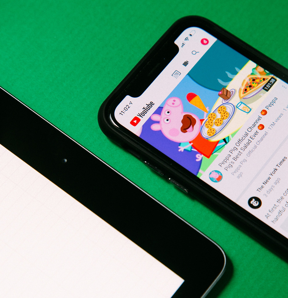 A smartphone showing the cartoon Peppa Pig on YouTube with a tablet next to it