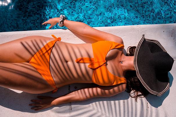 Lady sunbathing beside a pool