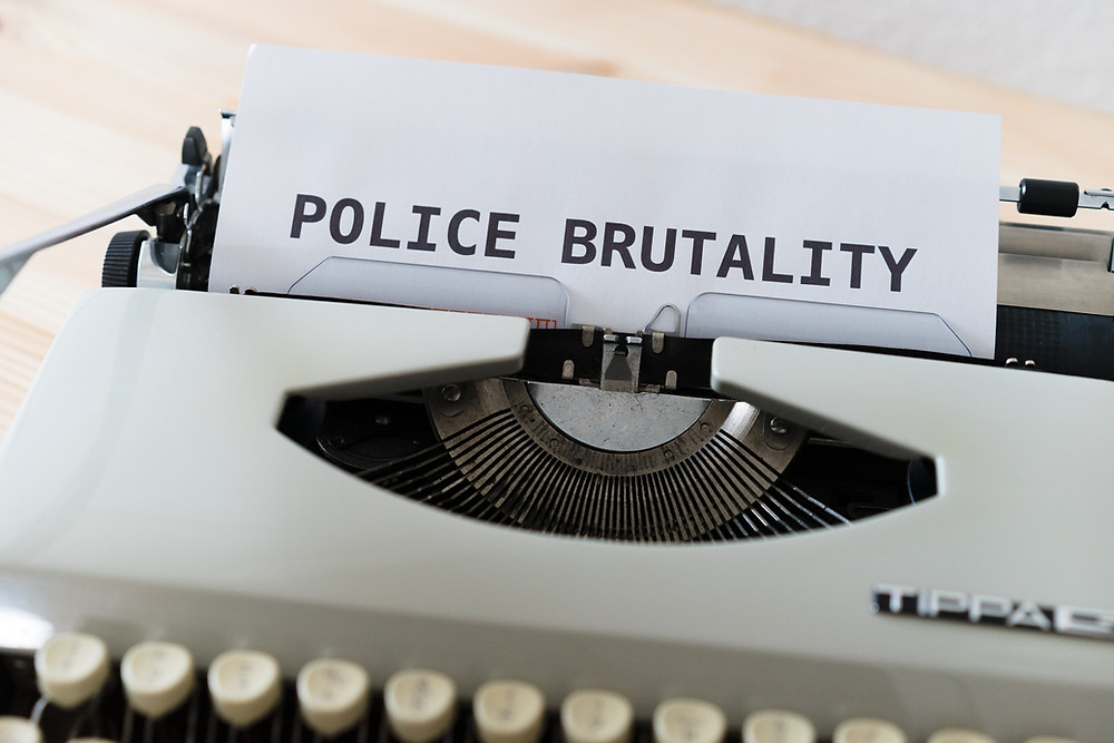 "letter coming out of typewriter that says ""police brutality"" in bold letters"