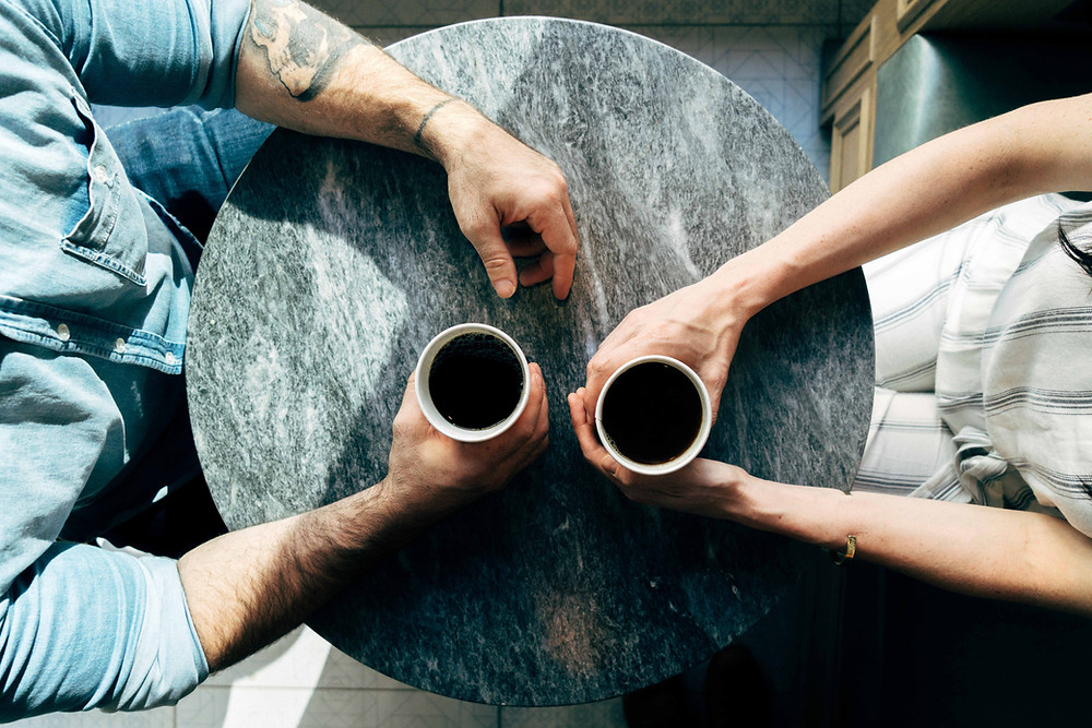 an arial view of a round cafe table with two cups of coffee, each one held by two hands