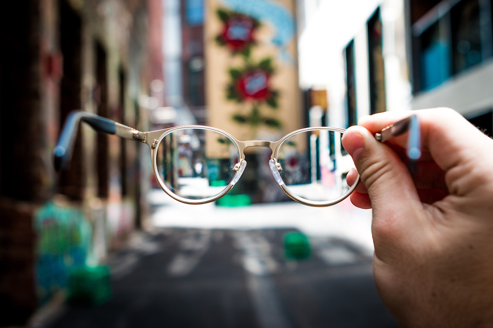 Person holding up glasses to view out of focus city street.