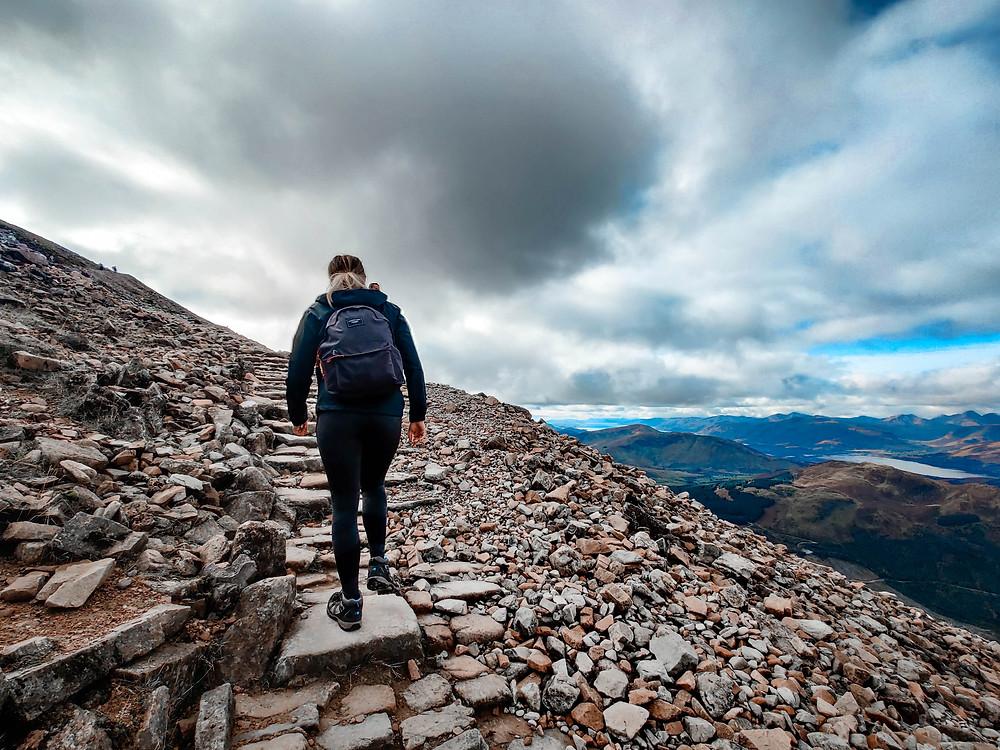 Nainen kiipeämässä vuorelle.