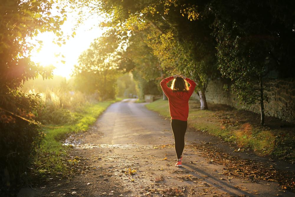 Frau steht auf einem Waldweg und betrachtet Sonnenuntergang