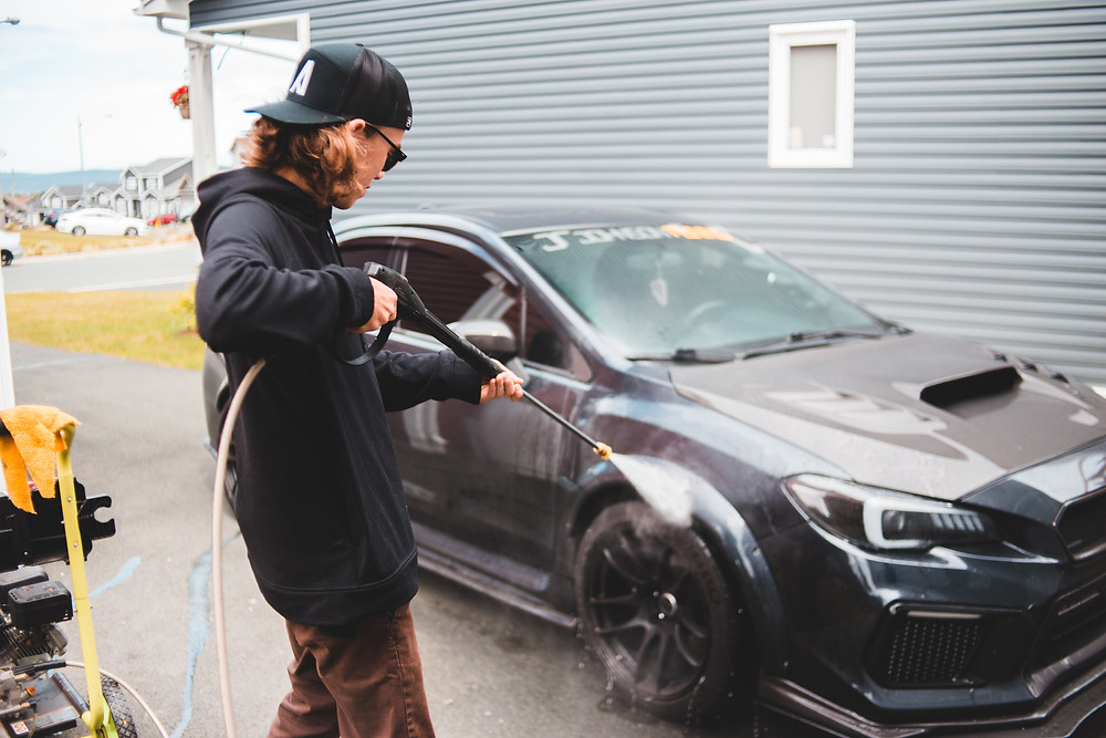 young guy washing his car