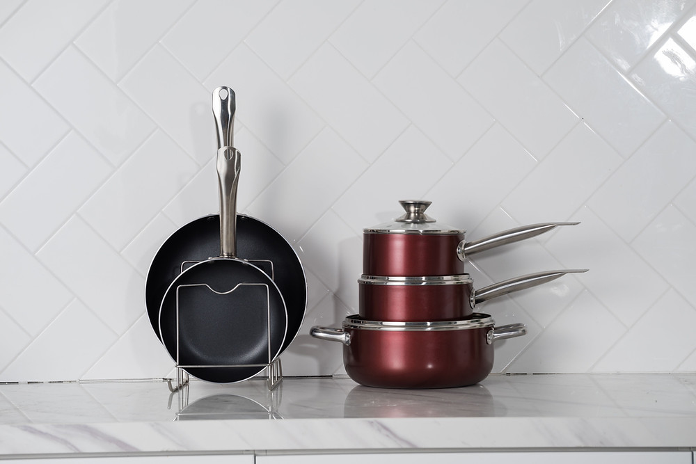 Clean pots and pans sitting on kitchen marble countertop