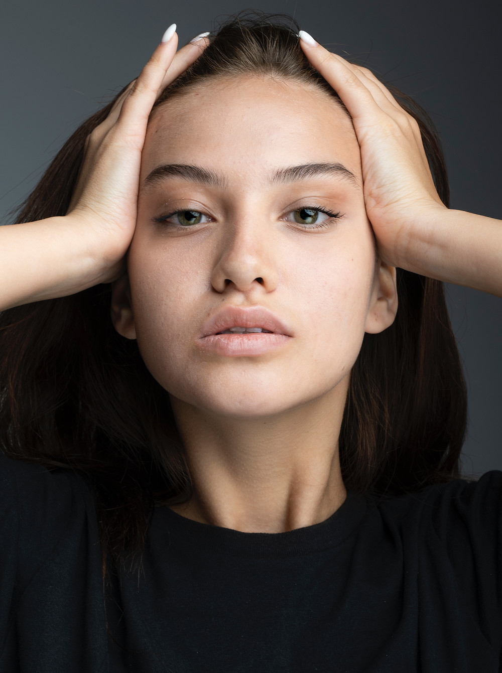 a woman pulling her hair back looking tired