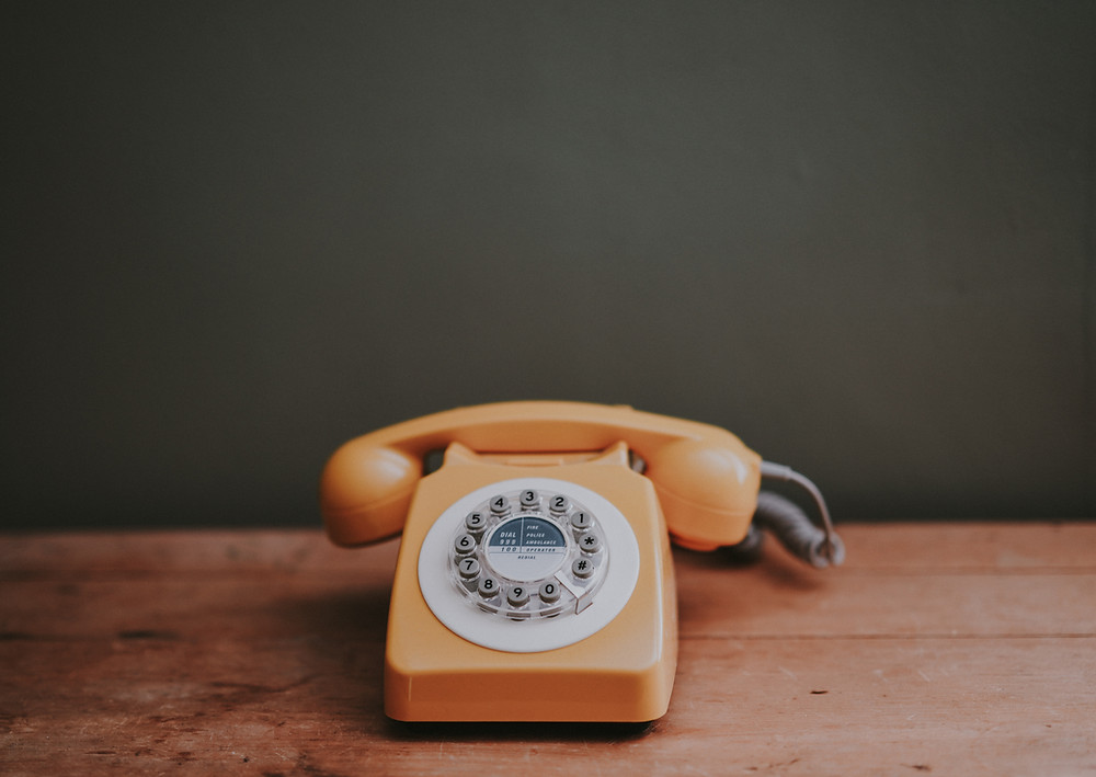 A rotary dial phone on a wooden table.