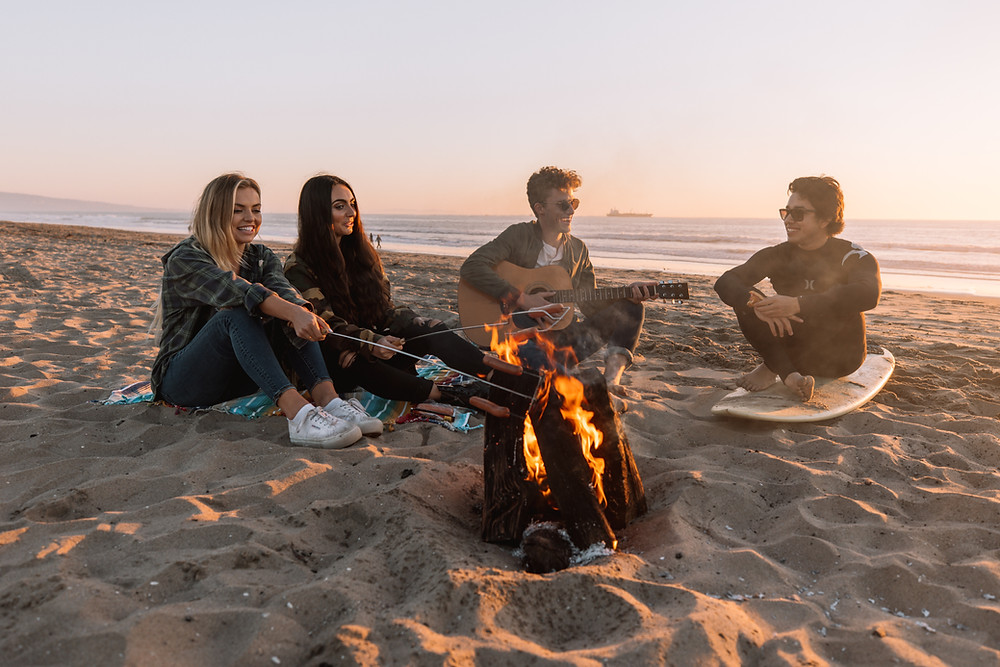 four people at a campfire on the beach