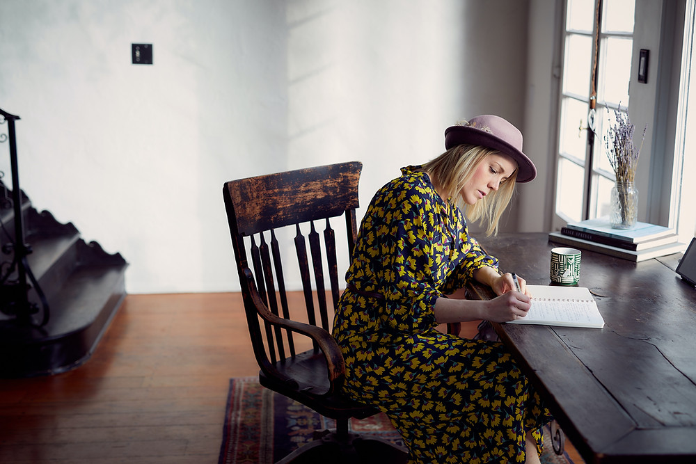 woman writing in book on wooden desk