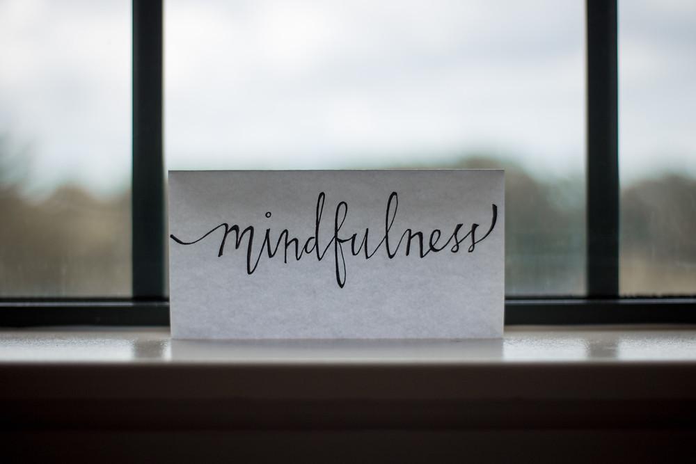Zettel mit Aufschrift mindfulness aufgestellt an einem Fenster
