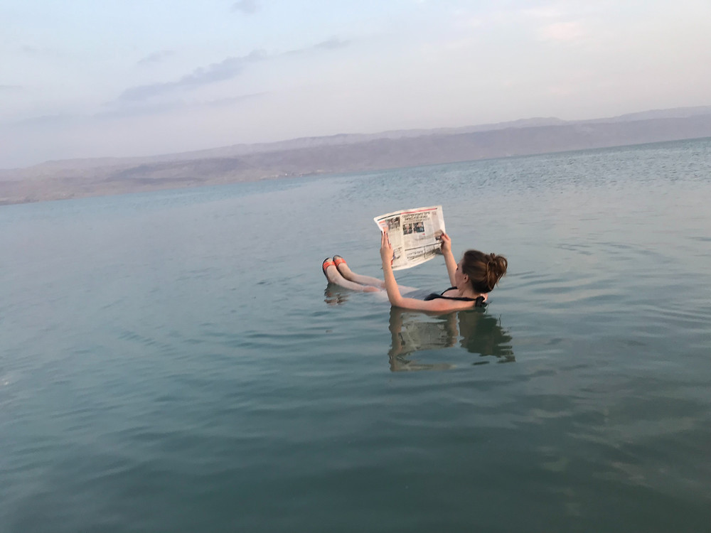 Woman floating in the Dead Sea while reading a newspaper