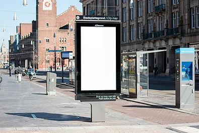 Digital signage kiosk on sidewalk along a street.