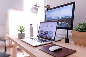 An orderly, stylish, office with an open laptop showing a website; a second, larger screen; a mousepad and mat; a drink; and a plant.