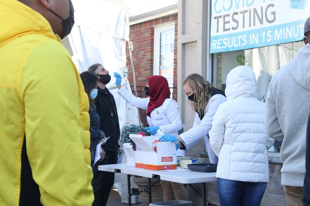 Photo ID: A woman in a purple hijab swabs a man's nose at a public COVID-19 testing site.