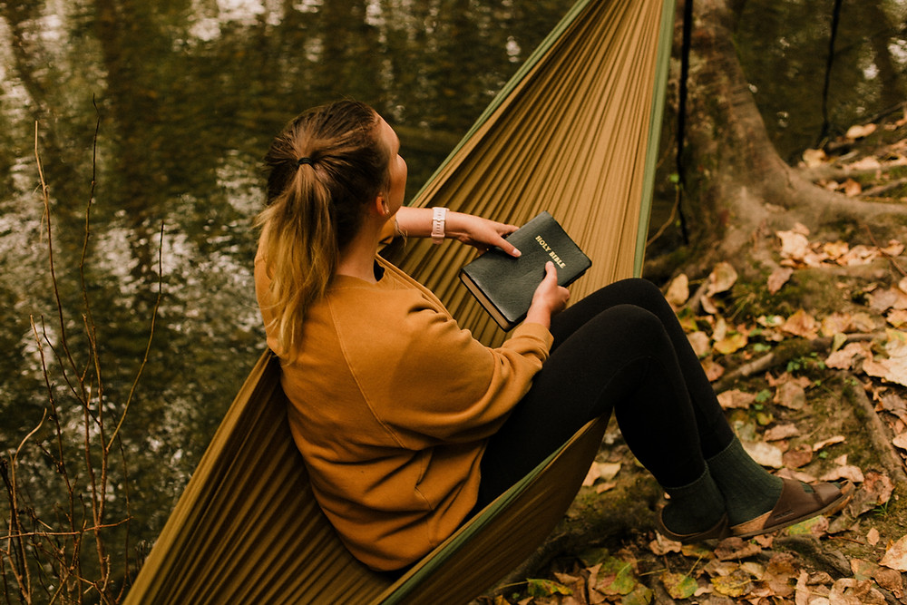 Woman sitting in a hammock with a book