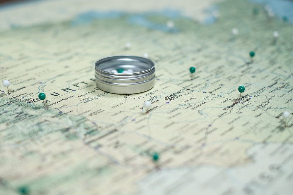 Photo of a map with green pins stuck in the map to mark places