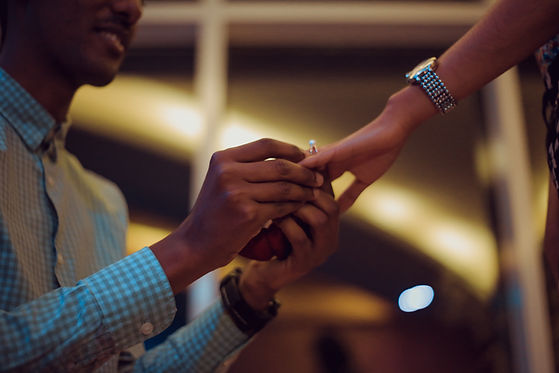 Man on one knee fitting a ring on a woman's finger