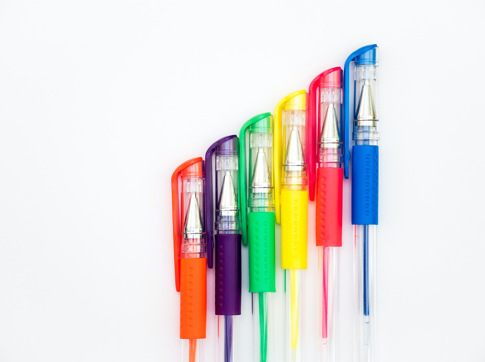organized line of gel pens in multiple colors on a white background