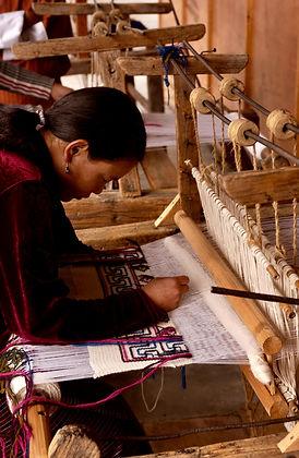 Rug weaver weaving a rug on a loom.