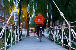 Man riding a bike over a bridge