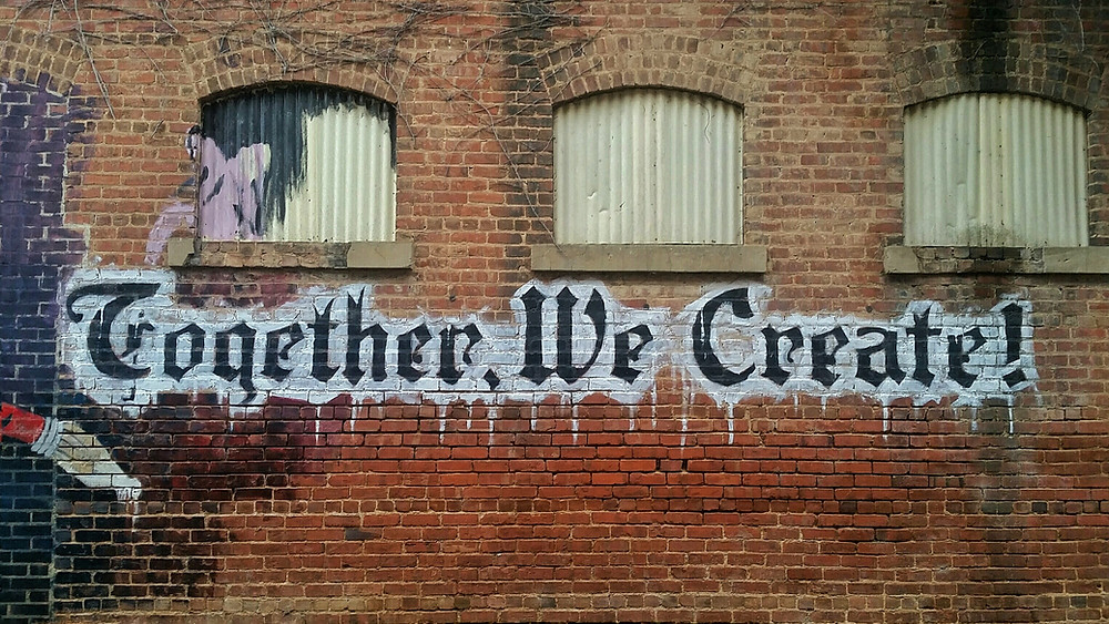 An Old Brick will with Blocked out windows, written in an old fashions gothic font are the Words in Graffiti style, Together, We Create