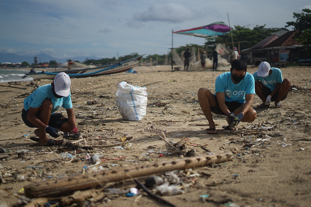 3 pessoas com camisas brancas, shorts pretos e bonés, retirando lixo de uma praia.