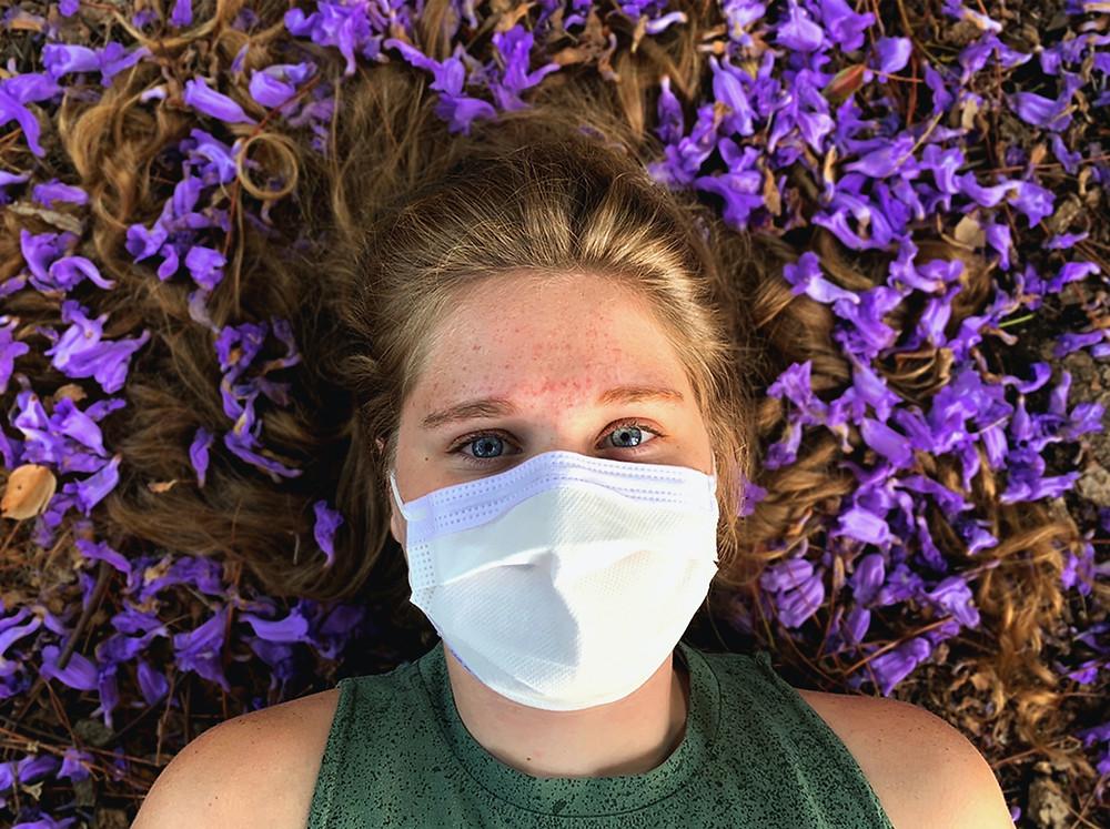 Frau mit medizinischer Maske liegt in lila Blüten.