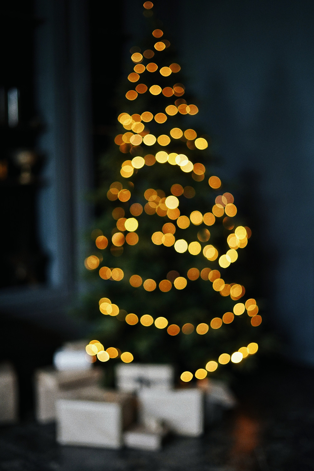 Out of focus Christmas tree with presents underneath it.