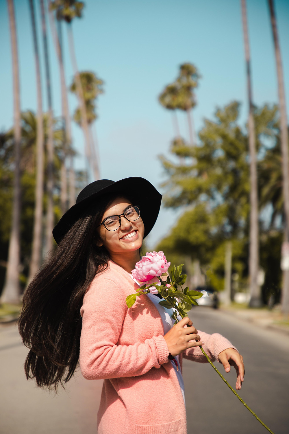 Young women wearing a pink sweater holds a pink flowers in the middle of a sunny street