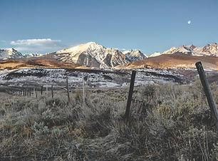 Snowcapped mountain peaks loom over the prairies in Colorado, USA. Plan my trip to Colorado