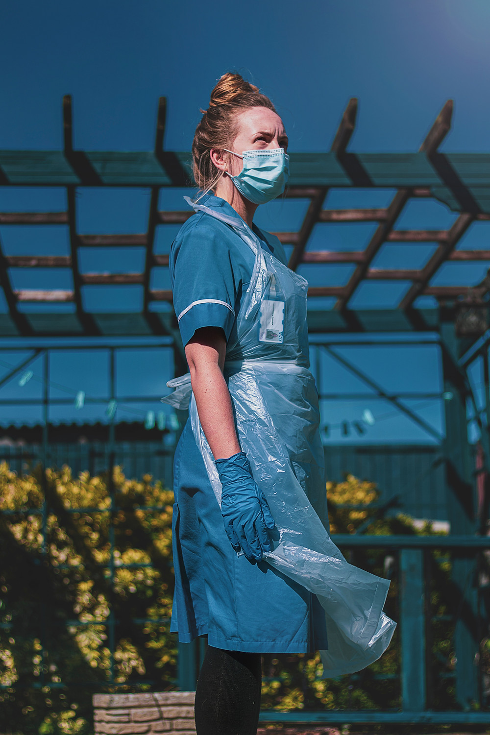 Female nurse standing in outside in the sun in full Covid-19 PPE.