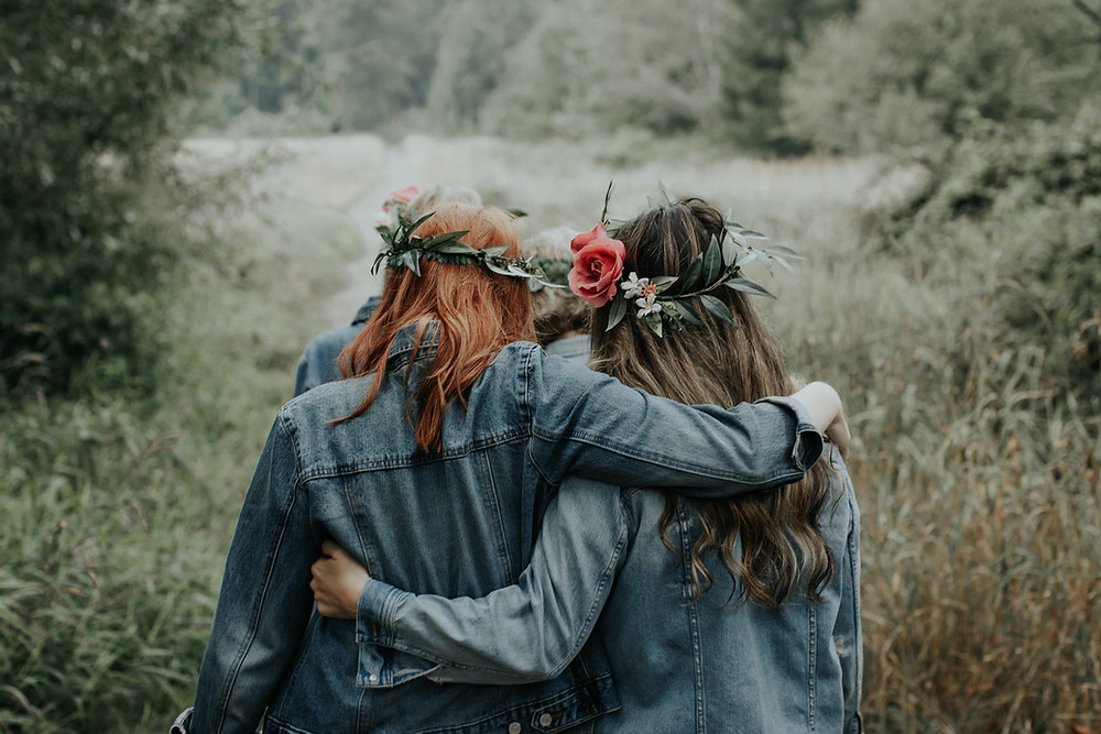 women arm in arm wearing flower crowns and denim jackets