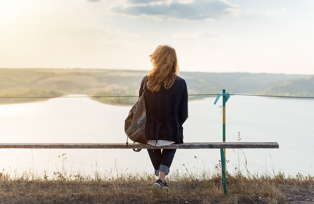 woman sitting on a bench with a backpack looking at the ocean