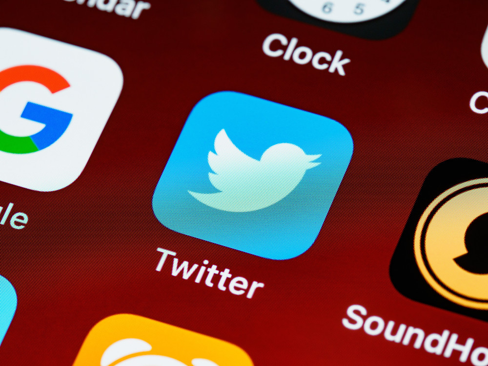 imagem de várias redes sociais em uma tela com a logo do twitter ao centro