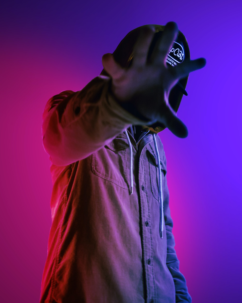 Man hiding his face with his hand while his background is lit - OnecomShop