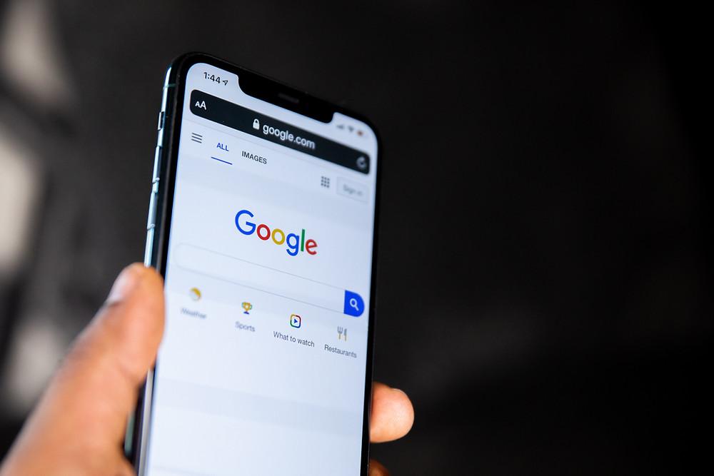 Pessoa segurando smartphone com página do Google aberta
