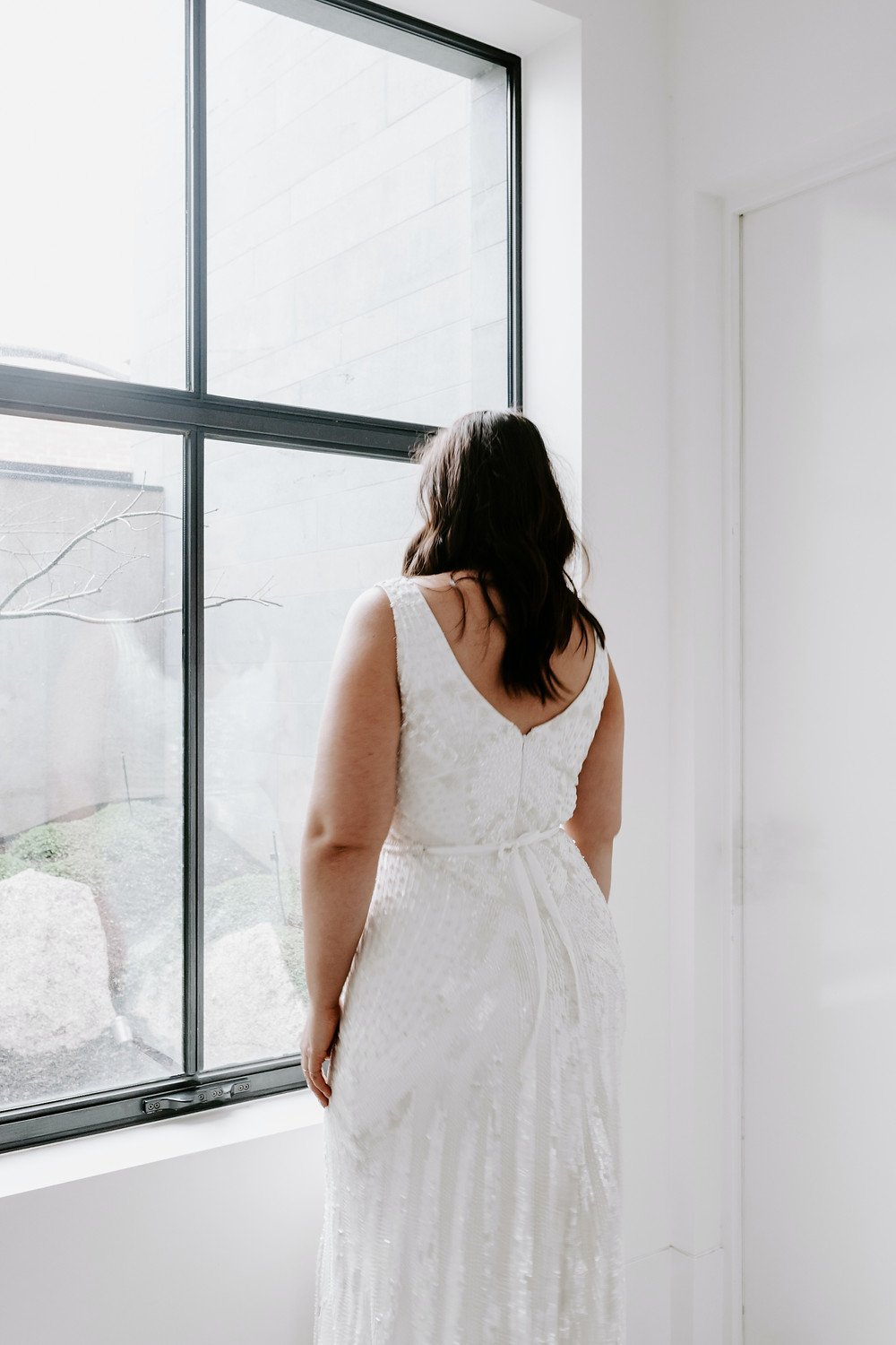 curvy bride in wedding dress looking out the window