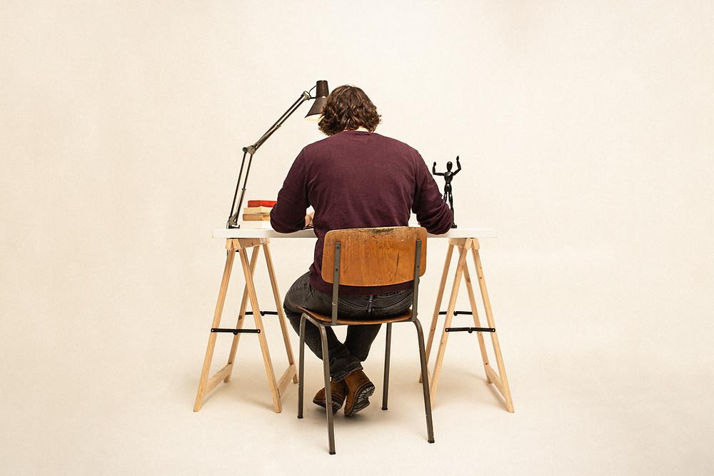 Homem sentado em uma cadeira em frente a uma mesa com luminária e alguns livros