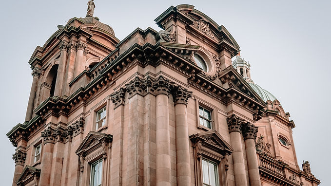 Am Image of an elegant European building in pink stone. A bank?