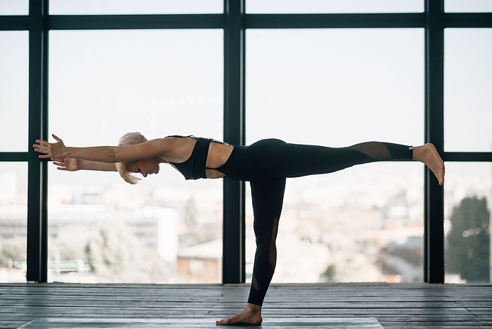 Woman perfecting a difficult yoga posture that requires strength and balance