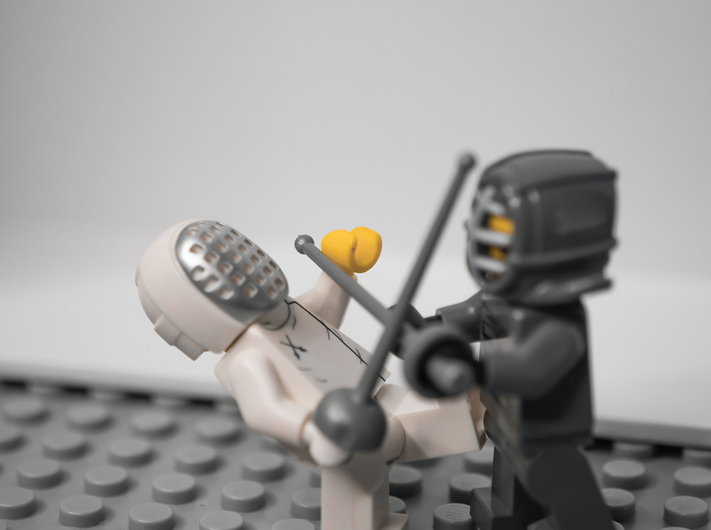 Two LEGO figures fencing.