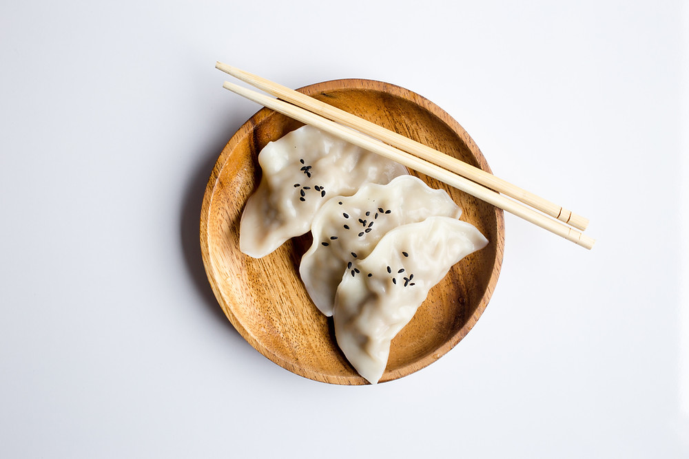 Three dumplings in a wooden bowl next to chopsticks.