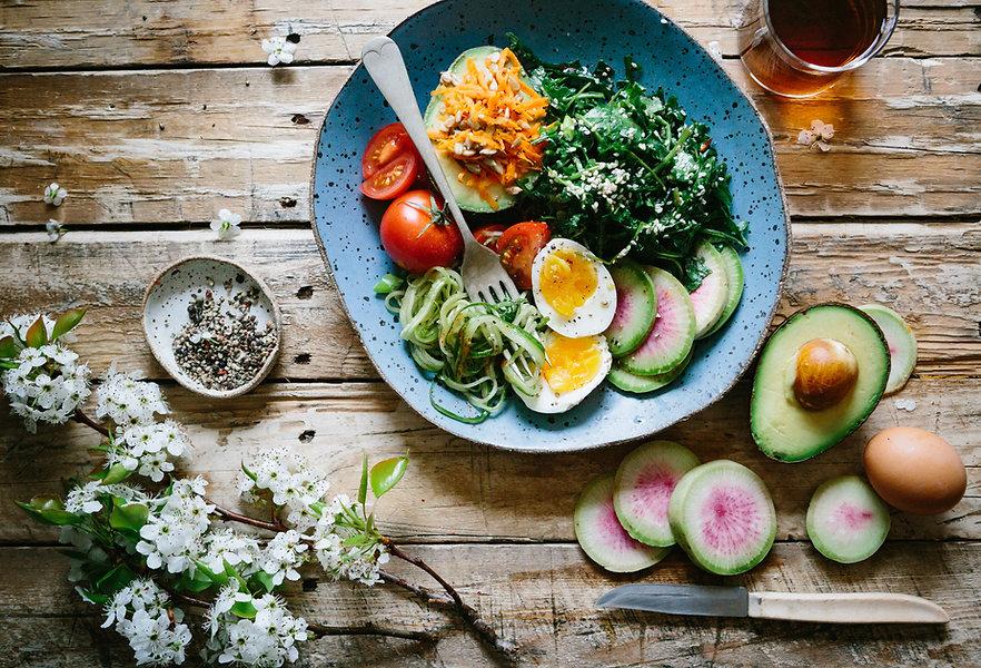 Image by Brooke Lark lautasella ketoystävällistä salaattia, kananmunaa, kurkkua, tomaattia, retikkaa, lehtikaalia ja avokadoa.