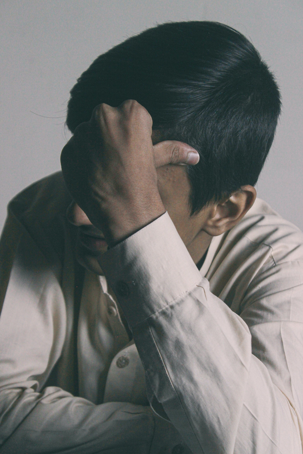 A South Asian male leans on his elbow and anxiously thinks to himself.
