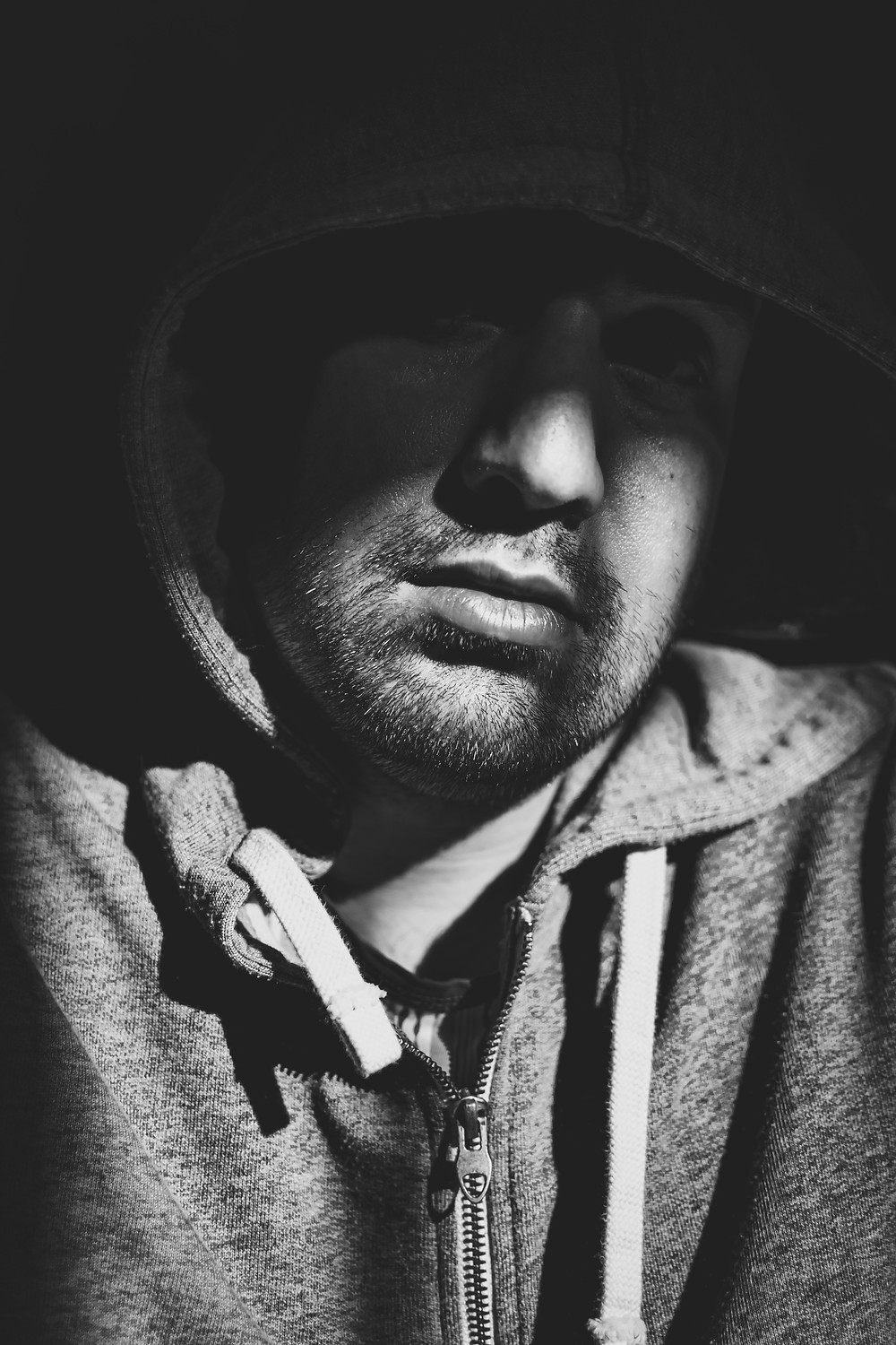 Man in hoodie, partially hidden in shadows, with stubble on face