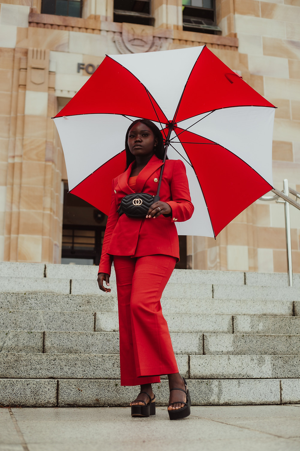 Woman in bold red outfit with white and black umbrella.